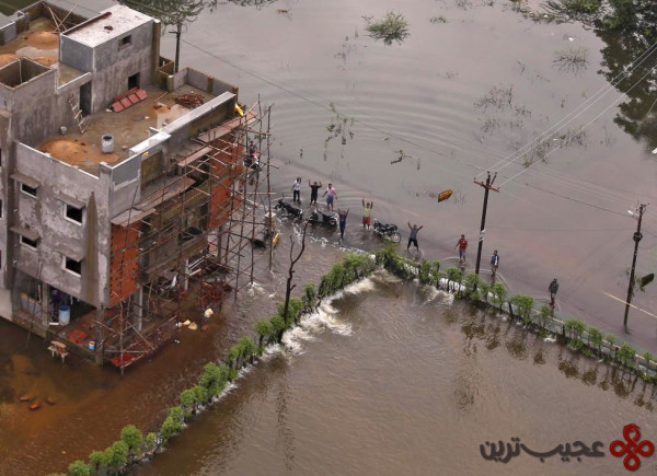 Flood-affected people gesture to an Indian coast guard helicopter for relief materials in Chennai