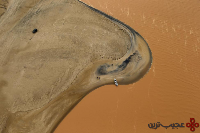 A boat is seen on the mouth of Rio Doce (Doce River), which was flooded with mud after a dam owned by Vale SA and BHP Billiton Ltd burst, as the river joins the sea on the coast of Espirito Santo in Regencia Village