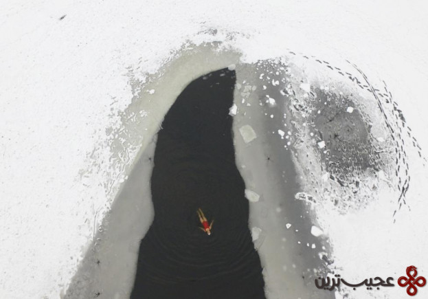 A woman swims in a partially frozen lake at a park in Shenyang